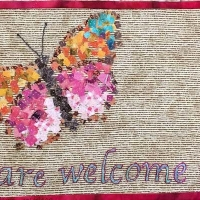 This piece is a welcome mat to all that seek refuge in our country. The fabric butterfly is representative of the migration of people to a better, safer life.