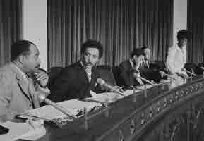 Long desk with 3 black male legislators and Shirley Chisholm sitting behind