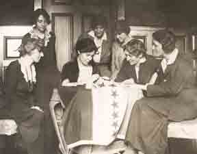 Alice sits at table sewing a star to a banner for each state that ratifies the 19th amendment.
