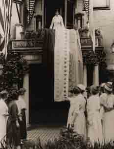 Alice Paul stands on balcony with star banner hanging down. Many women standing on ground below looking up.