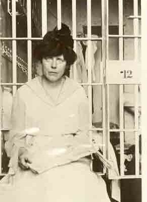 Lucy Burns sits before a jail cell door possibly holding newspaper containing published account of the Night of Terror.