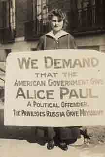 "Young woman stands holding banner that reads, ""We Demand that the American Government Give Alice Paul, a political offender, the privileges Russia gave Miyukoff"