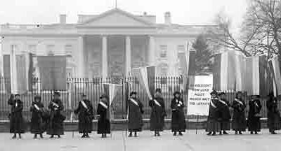 suffragette movement deploys women to line up in front of White House to pressure Pres. Wilson to support 19th amendment inspired the presentation of Lucy on the Women's Work quilt holding a picket sign.