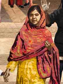 Malala shown walking forward wearing a golden kaftan with a red scarf.
